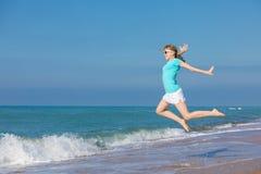 Muchacha adolescente que salta en la playa en la orilla de mar azul en vacat del verano Foto de archivo