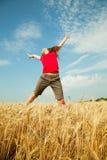 Muchacha adolescente que salta en un campo de trigo Foto de archivo libre de regalías