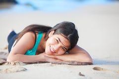 Muchacha adolescente que se acuesta en la playa arenosa, cabeza en los brazos Imagen de archivo