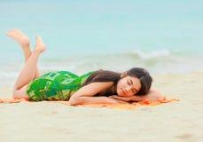 Muchacha adolescente que se acuesta en la playa hawaiana, descansando por el océano Fotografía de archivo libre de regalías