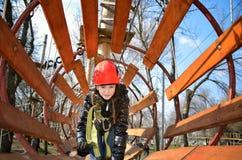 Muchacha adolescente que se arrastra en un laberinto de madera redondo en el parque en el spr Fotografía de archivo libre de regalías