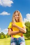 Muchacha adolescente que se coloca con el libro Fotografía de archivo libre de regalías