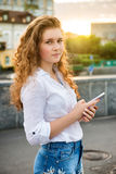 Muchacha adolescente que se coloca con el teléfono móvil al aire libre Fotos de archivo libres de regalías