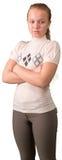 Muchacha adolescente que se coloca con las manos cruzadas aisladas encendido Foto de archivo libre de regalías