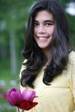 Muchacha adolescente que se coloca con los tulipanes Fotos de archivo libres de regalías