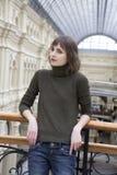 Muchacha adolescente que se coloca en cercar con barandilla en almacén grande en Mosc Fotografía de archivo