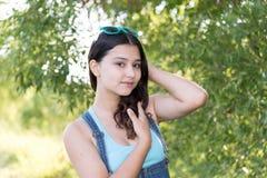 Muchacha adolescente que se coloca en el fondo de madera Foto de archivo