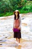 Muchacha adolescente que se coloca en el río bajo Fotos de archivo
