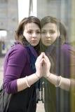 Muchacha adolescente que se coloca en la pared de cristal Imagen de archivo