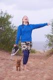 Muchacha adolescente que se coloca en la playa con su perro Fotografía de archivo