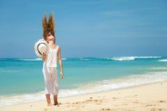 Muchacha adolescente que se coloca en la playa en la orilla de mar azul en el verano VAC Fotos de archivo