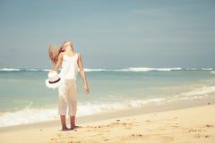 Muchacha adolescente que se coloca en la playa en la orilla de mar azul en el verano VAC Imagen de archivo