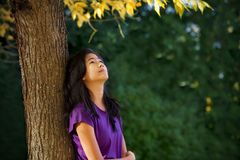 Muchacha adolescente que se inclina contra árbol con las hojas de otoño que miran para arriba Fotografía de archivo