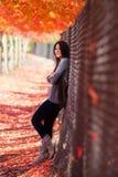 Muchacha adolescente que se inclina contra la cerca debajo del toldo de los árboles de arce Fotos de archivo libres de regalías
