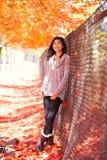 Muchacha adolescente que se inclina contra la cerca debajo del toldo de los árboles de arce Foto de archivo