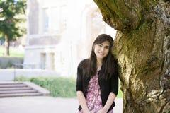 Muchacha adolescente que se inclina contra tronco de árbol grande Fotos de archivo