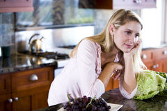 Muchacha adolescente que se inclina en el contador de cocina que soña despierto Imagen de archivo