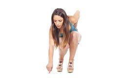 Muchacha adolescente que se pone en cuclillas y que señala en el suelo Imagenes de archivo