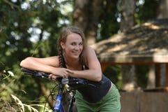 Muchacha adolescente que se reclina sobre los manillares de la bicicleta Fotos de archivo