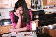 Muchacha adolescente que se relaja en cocina Fotos de archivo libres de regalías