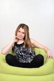 Muchacha adolescente que se relaja en silla del puf Fotos de archivo