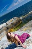 Muchacha adolescente que se relaja en una costa de mar Foto de archivo