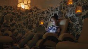 Muchacha adolescente que se relaja en una cueva de la sal en halotherapy almacen de metraje de vídeo