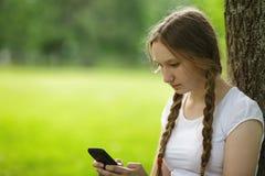 Muchacha adolescente que se sienta cerca de árbol con el teléfono móvil Imagen de archivo