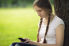 Muchacha adolescente que se sienta cerca de ?rbol con el tel?fono m?vil Imagenes de archivo