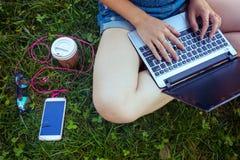 Muchacha adolescente que se sienta con una computadora portátil Foto de archivo