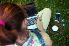 Muchacha adolescente que se sienta con una computadora portátil Imagen de archivo
