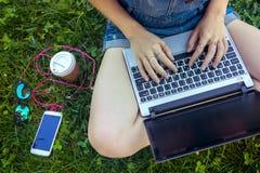 Muchacha adolescente que se sienta con una computadora portátil Fotos de archivo