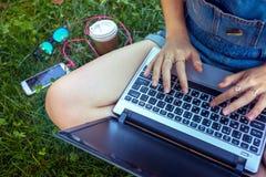 Muchacha adolescente que se sienta con una computadora portátil Fotografía de archivo libre de regalías