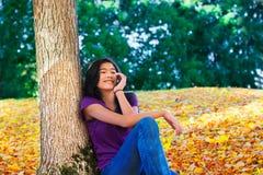 Muchacha adolescente que se sienta contra árbol del otoño usando el teléfono celular Fotografía de archivo