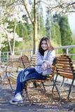 Muchacha adolescente que se sienta en banco bajo cerezo Imagenes de archivo