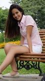 Muchacha adolescente que se sienta en banco de parque Imagenes de archivo