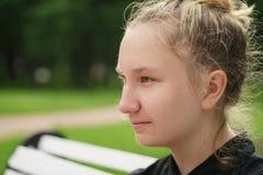 Muchacha adolescente que se sienta en banco en parque Imagenes de archivo