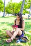 Muchacha adolescente que se sienta en césped de la hierba usando smartphone en verano Fotografía de archivo
