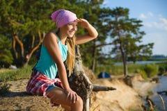 Muchacha adolescente que se sienta en el acantilado de la arena que mira al mar Concepto del recorrido y del turismo Foto de archivo