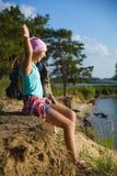 Muchacha adolescente que se sienta en el acantilado de la arena que mira al mar Concepto del recorrido y del turismo Imagen de archivo
