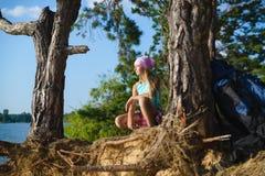 Muchacha adolescente que se sienta en el acantilado de la arena que mira al mar Concepto del recorrido y del turismo Fotografía de archivo