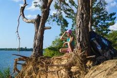 Muchacha adolescente que se sienta en el acantilado de la arena que mira al mar Concepto del recorrido y del turismo Fotos de archivo