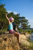 Muchacha adolescente que se sienta en el acantilado de la arena que mira al mar Concepto del recorrido y del turismo Imágenes de archivo libres de regalías