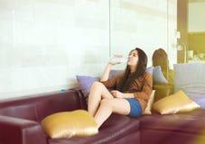 Muchacha adolescente que se sienta en el agua embotellada de consumición del sofá Imágenes de archivo libres de regalías