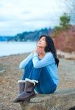 Muchacha adolescente que se sienta en el canto rodado a lo largo de la rogación de la orilla del lago Imagen de archivo libre de regalías