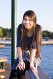 Muchacha adolescente que se sienta en el lago de desatención de la verja Fotografía de archivo libre de regalías