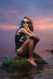 Muchacha adolescente que se sienta en el lanzamiento de piedra de la moda en la puesta del sol Imágenes de archivo libres de regalías