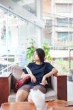 Muchacha adolescente que se sienta en el pasillo del hotel que mira hacia fuera la ventana, agujereada Imagenes de archivo