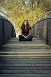 Muchacha adolescente que se sienta en el puente Fotos de archivo