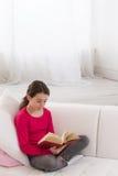 Muchacha adolescente que se sienta en el sofá en casa y que lee a Imagenes de archivo